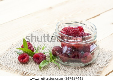 Fresh sweet red raspberry in a glass jar and mint on light wooden table, selective focus