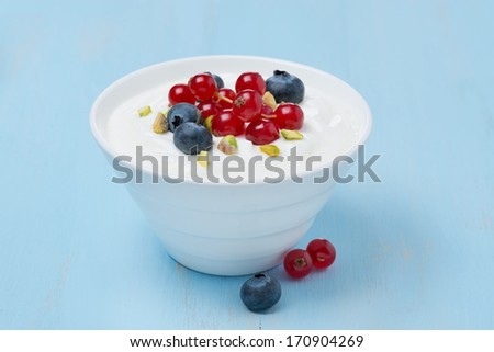 fresh sweet yogurt with berries and pistachios in a bowl, close-up - stock photo