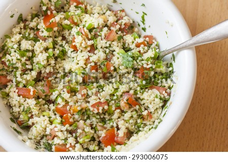 Fresh tabbouleh, a Middle Eastern salad, in a white bowl - stock photo