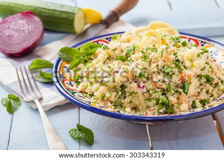 fresh tabbouleh on decorated bowl over wooden table