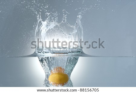 fresh tangerine dropped into water - stock photo