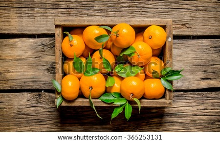 Fresh tangerines in an old box with leaves. On wooden background.  Top view - stock photo