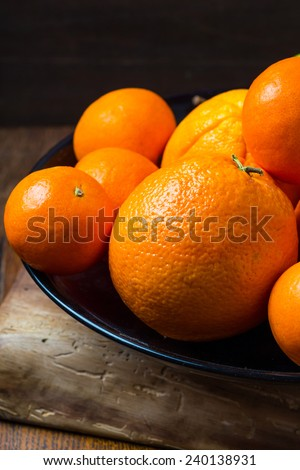Fresh tangerines in bowl on wooden table - stock photo