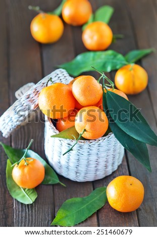 fresh tangerines in the white basket and on a table - stock photo