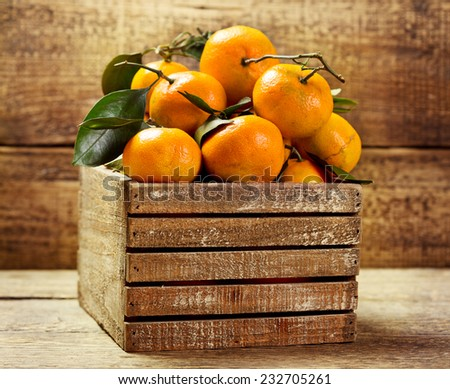fresh tangerines with leafs in wooden box - stock photo