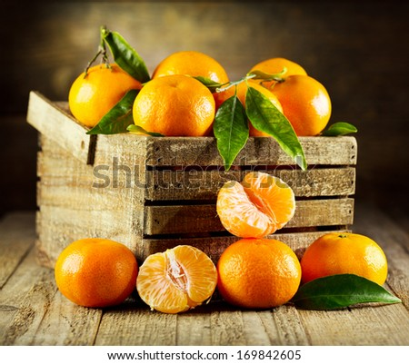 fresh tangerines with leaves in wooden box - stock photo