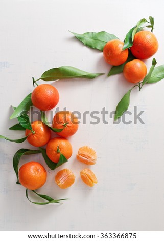 Fresh tangerines with leaves on table - stock photo