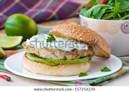 Fresh, tasty chicken burger in the Greek style with zucchini and yogurt cucumber sauce tzatziki, lime, salad