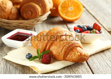 Fresh tasty croissants with berries on grey wooden background - stock photo