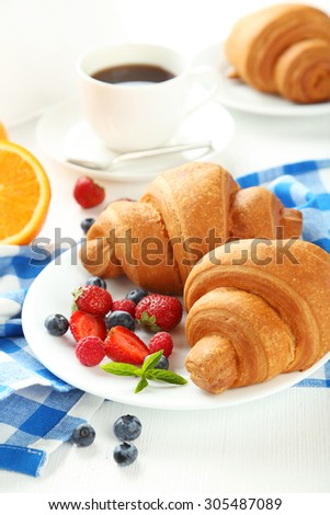 Fresh tasty croissants with berries on white wooden background - stock photo
