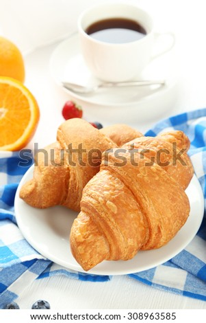 Fresh tasty croissants with strawberry and coffee on white wooden background - stock photo