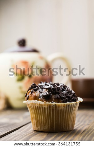 Fresh tasty dessert chocolate muffin in paper basket on wooden table in background of cute teapot unhealthy food with many calories culinary copyspace indoor closeup on light background, vertical - stock photo