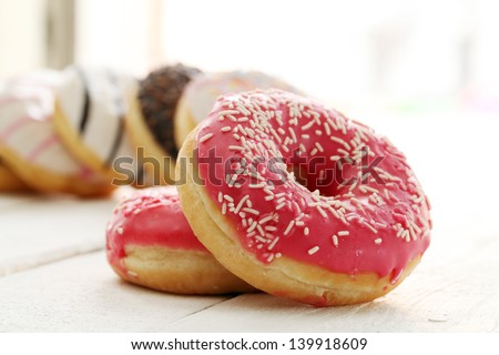 Fresh tasty donuts with glaze on a white table - stock photo