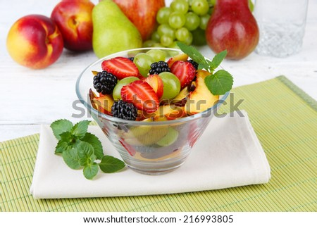 fresh tasty fruit salad on table - stock photo