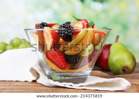 fresh tasty fruit salad on wooden table, on nature background - stock photo