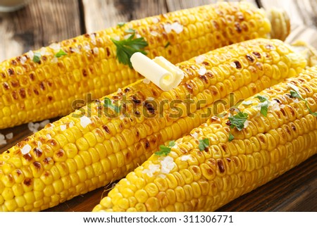 Fresh tasty grilled corn with butter on brown table - stock photo