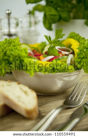 fresh tasty healthy mixed salad and bread on wooden table - stock photo