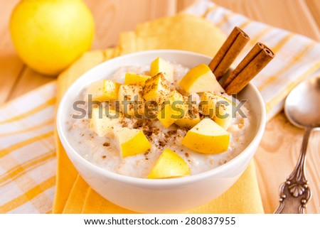 Fresh tasty hot oatmeal porridge with apple slices and cinnamon on napkin and wooden table. Healthy natural organic breakfast close up vertical. - stock photo