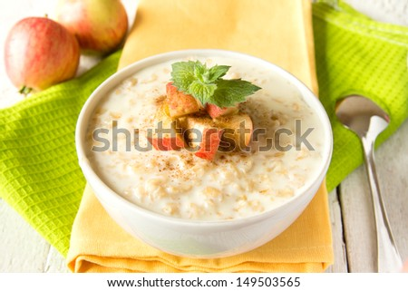 Fresh tasty hot oatmeal porridge with apple slices, mint, cinnamon and spoon on napkin and wooden table. Healthy natural vegetarian breakfast close up horizontal. - stock photo