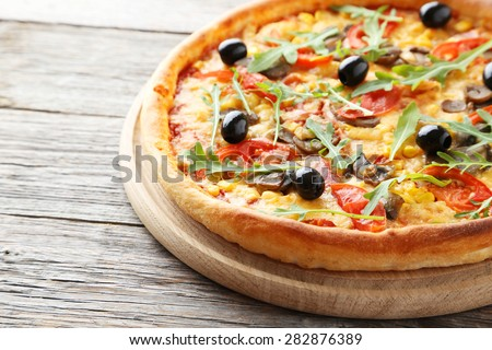 Fresh tasty pizza on grey wooden background - stock photo