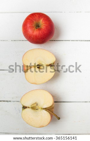 Fresh tasty red apple fruits isolated on a white wooden background.