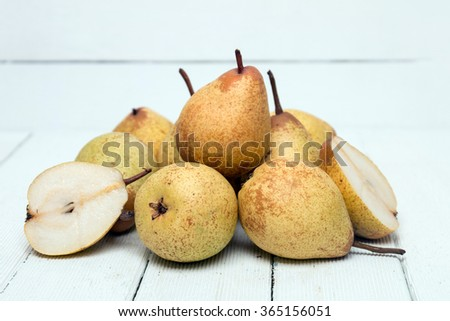 Fresh tasty yellow pear fruits isolated on a white wooden background. - stock photo