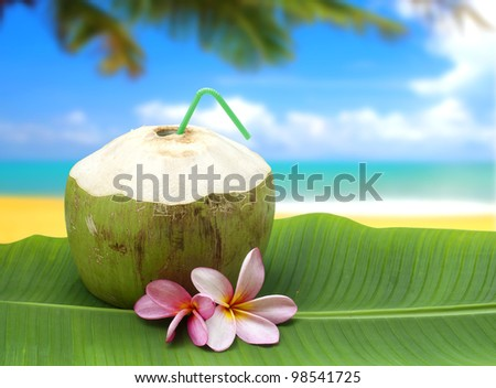 fresh tender green coconut drink on tropical beach - stock photo