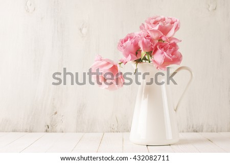 Fresh tender pink garden roses in white jug on rustic white wooden background. Filtered retro stylized image.