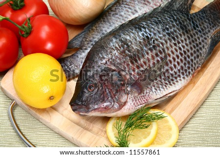 Fresh Tilapia with tomato, lemon, dill on cutting board.  St. Peter's fish. - stock photo