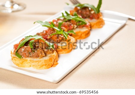 fresh tipycal italian bruschetta with tomato and arugula on top - stock photo
