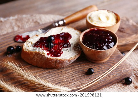 Fresh toast with homemade butter and blackcurrant jam on wooden background - stock photo