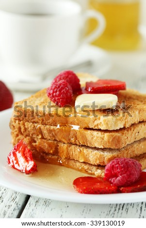 Fresh toast with raspberry and strawberry on white wooden background