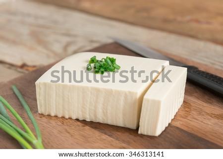 Fresh tofu on cutting board. - stock photo