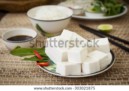 Fresh tofu with rice, salad and soy sauce on a wooden background - stock photo