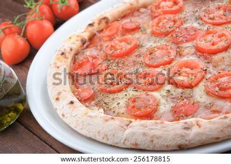 Fresh tomato and mozzarella pizza on wooden table - stock photo