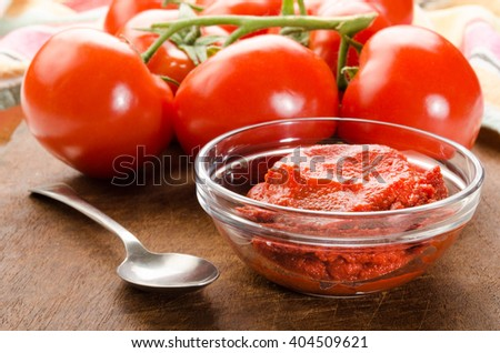 fresh tomato and paste in a glass bowl on wooden board - stock photo