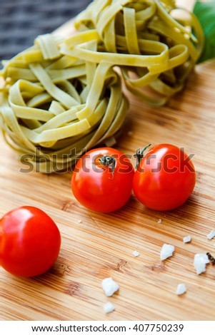 Fresh tomato and spaghetti (pasta) with Basil and a mixture of peppers on the Board