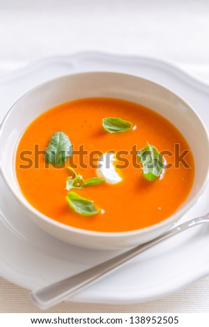 fresh tomato cream soup garnished with basil in a bowl - stock photo
