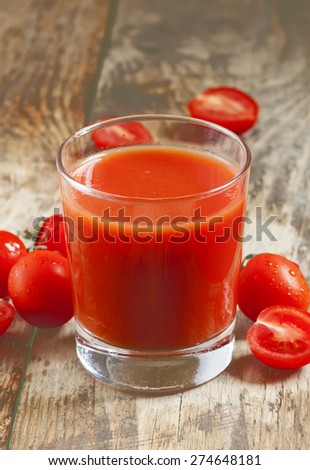 Fresh tomato juice and tomatoes on the table, selective focus