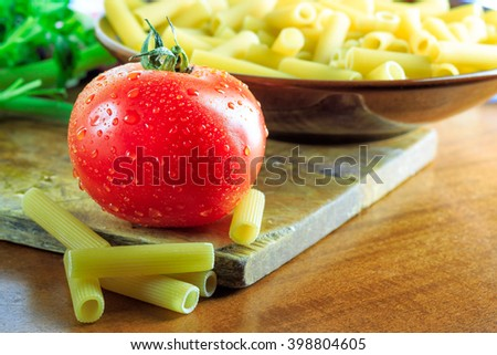 Fresh tomato next to plate full of raw uncooked macaroni. Copy space