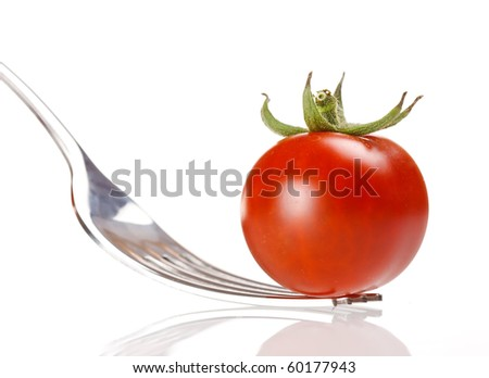 fresh tomato on the fork - stock photo