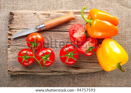 Fresh tomato, paprika, steel knife and vintage wooden cutting board on canvas tablecloth