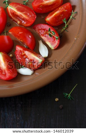 Fresh tomato salad with thyme and onion on a brown plate close up. - stock photo