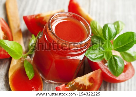 fresh tomato sauce jar with basil leaves - stock photo