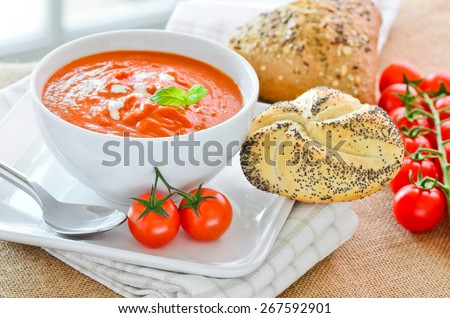Fresh tomato soup and fresh baked crusty bread rolls. - stock photo