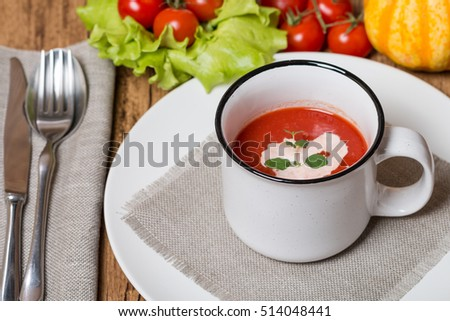 fresh tomato soup in a white bowl with ingredients
