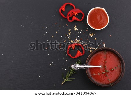 Fresh tomato soup in black bowl an ?hill cold soup, tomato juice - stock photo