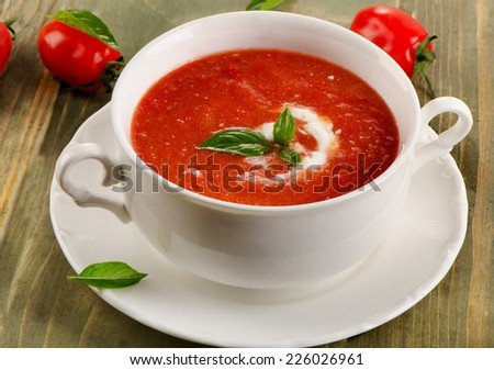 Fresh tomato soup in  white bowl on  wooden table