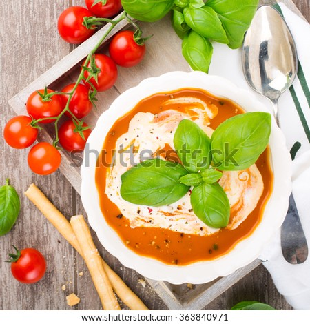 Fresh tomato soup  with basil and cream in a white bowl on wooden background. Top view.  - stock photo