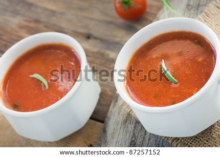 Fresh tomato soup with cherry tomatoes and fresh herbs and copyspace - stock photo